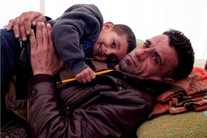 29 Novembre 2015 - Un padre iraniano abbraccia suo figlio di quattro anni in un campo improvvisato al confine greco-macedone nei pressi della città di Idomeni.